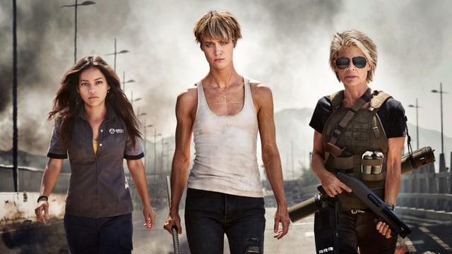 Eine braunhaarige und zwei blonde Frauen blicken in die Kamera. Die älteste hält eine Waffe.