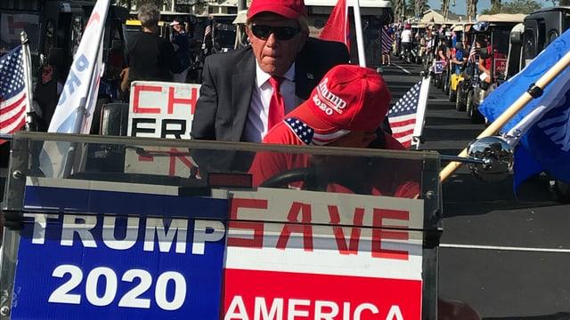 Ein als Donald Trump verkleideter Mann in einem Golfwagen mit Wahlplakaten.