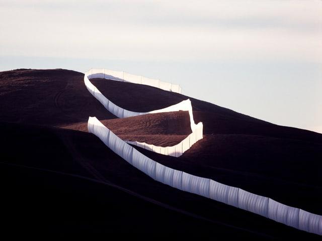 Ein Zaun aus Tüchern auf einem grossen Hügel.