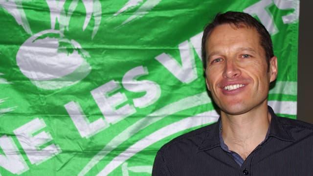 Christophe Clivaz steht vor dem Logo der Grünen Partei.