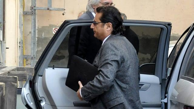 Schettino steigt mit einer Aktentasche unter dem Arm aus einem Auto.