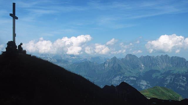 Ein Berg im Schatten. An der Spitze steht ein grosses Kreuz.
