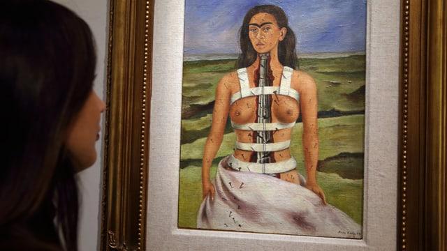 Eine Frau betrachtet ein Gemälde, das eine Frau mit einer antiken Säule anstelle einer Wirbelsäule zeigt