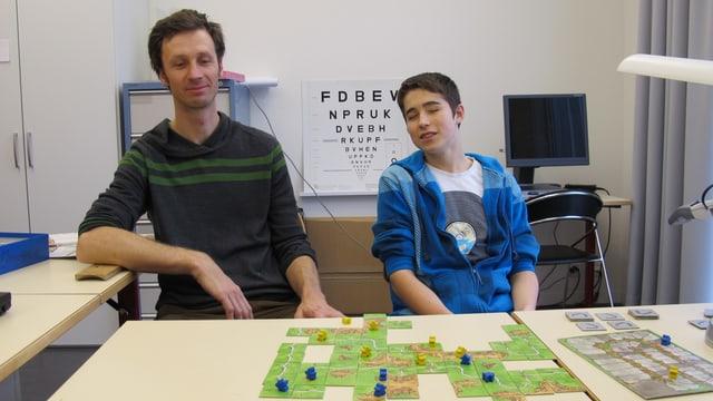 Matthias Rackl (links) und Kevin sitzen an einem Tisch, darauf Spielkarten mit Spielfiguren.