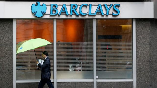Ein Banker in Anzug und mit Regenschirm läuft an einer Filiale der Barclays Bank vorbei.