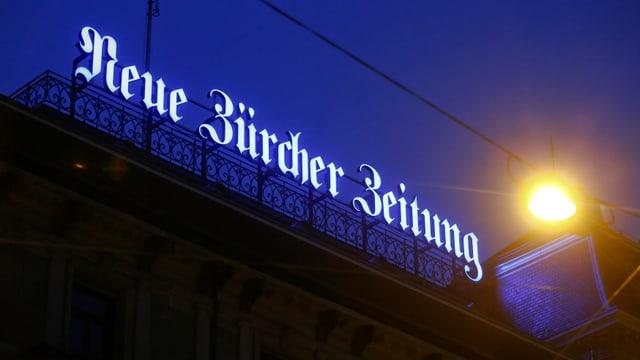 Logo da la Neuer Zürcher Zeitung sin il tetg da la centrala a Turitg.