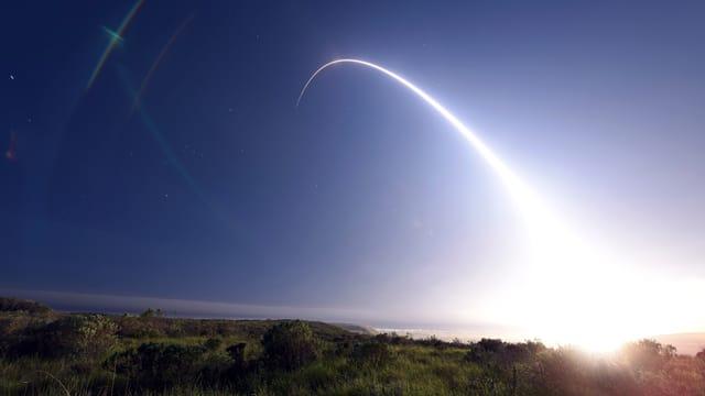 Raketenstart bei Nacht, man sieht die erleuchtete Flugkurve.