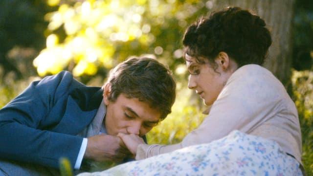 Ein Mann küsst die Hand einer Frau, die unter einem Baum liegt.