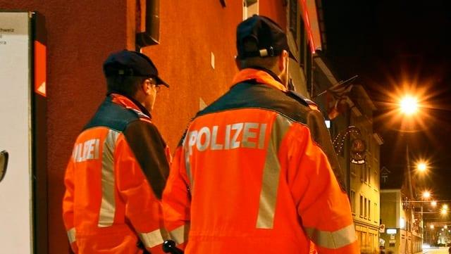Zwei Polizisten blicken in eine Gasse.