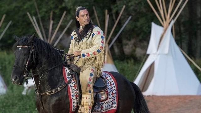 Ein als Winnetou kostümierter Mann auf einem Pferd.