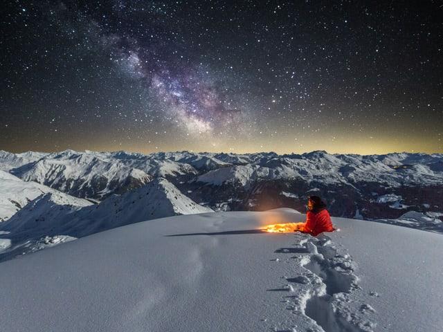 Nachtbild in den sternenklaren Alpen mit Schnee und gut sichtbarer Milchstrasse. Im Schnee sitzender Mensch.