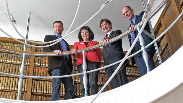 Vier Menschen schauen vom Balkon einer Bibliothek.