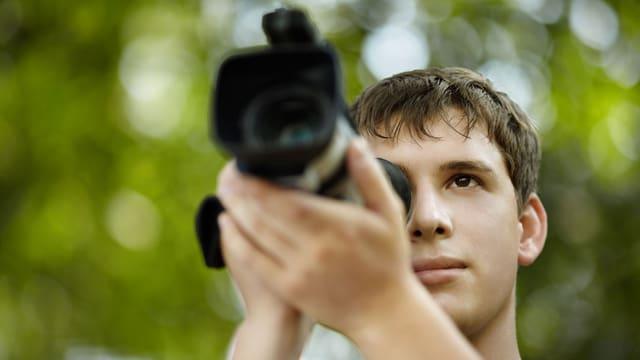 Ein junger Mann steht in der Natur und schaut durch den Sucher einer Videokamera.