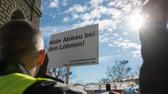 Ein Demonstrant hält ein Schild in die Höhe «Kein Abbau bei den Löhnen»