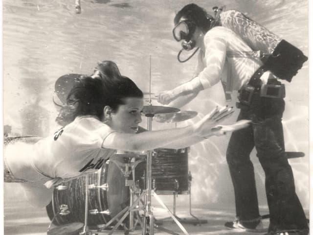 Schwarz-weiss-Bild eines Schlagzeugers, der mit Atemmaske unter Wasser spielt, im Vordergrund schwimmt eine Frau im T-Shirt vorbei.