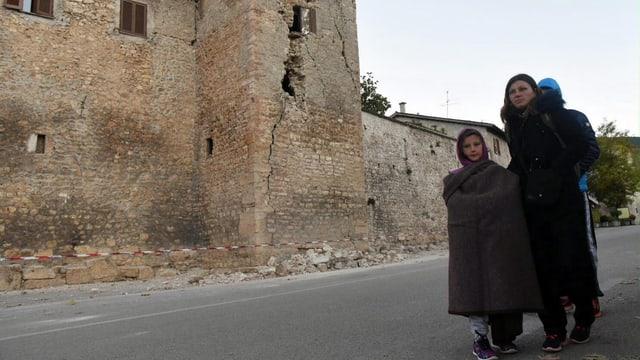 Frau mit zwei Kindern, in Wolldecke, vor einem beschädigten Haus mit Rissen.