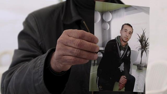 Ein Cousin Yassine al-Abidi hält ein Foto des mutmasslichen Attentäters hoch