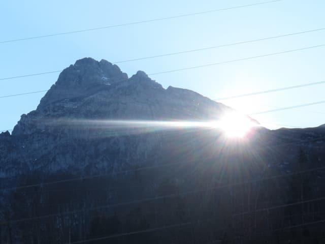 Die Sonne scheint durch das Mürtschenloch nach Obstalden/GL