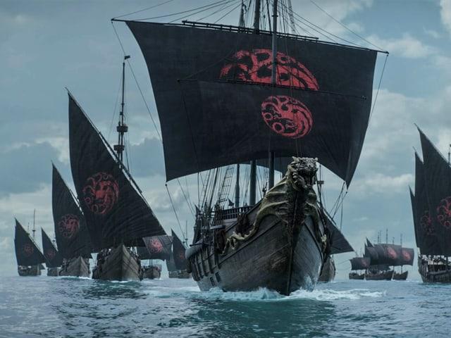 Einige Schiffe mit schwarzen Segeln und Drachenbild.
