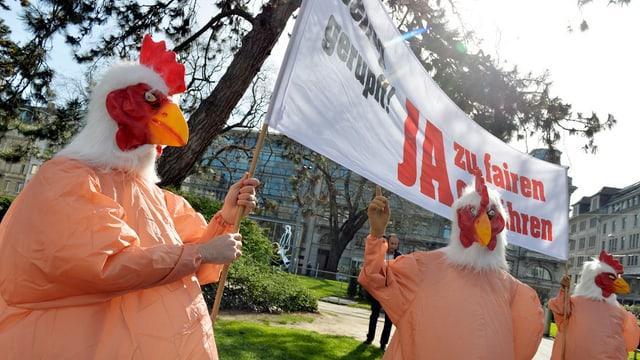 Demonstranten in Hühnerkostümen werben mit Transparent für Initiative «Ja zu fairen Gebühren».