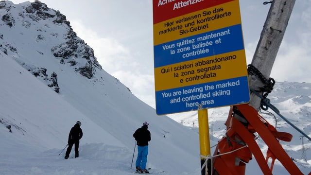 Zwei Skifahrer stehen hinter einem Warnschild.