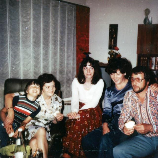 Drei Frauen, ein Mann und ein Bub sitzen in einem Wohnzimmer beieinander.