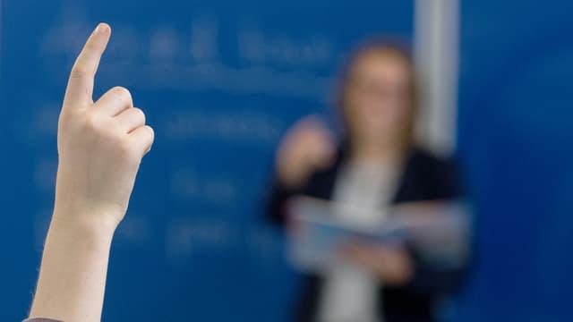 KInd in Klassenzimmer streckt Hand auf. Man sieht es von hinten. Vorne in der Unschärfe steht die Lehrerin.