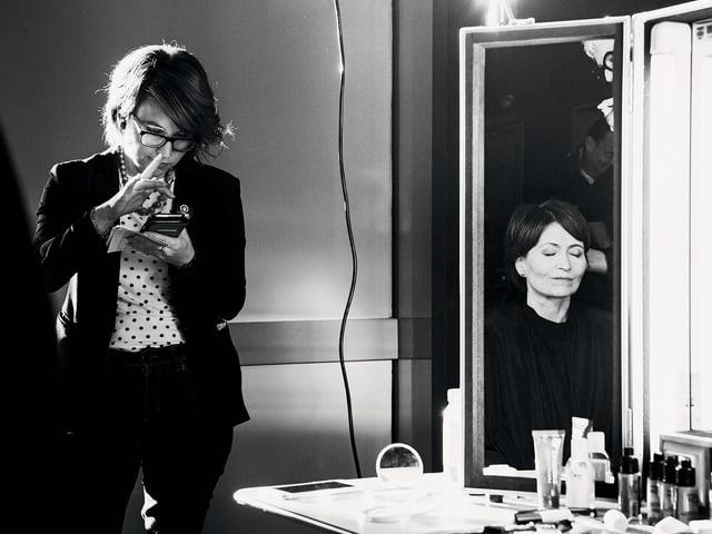 Schwarzweissbild: Eine Frau vor beleuchtetem Schminkspiegel, neben ihr stehend eine Frau am Smartphone