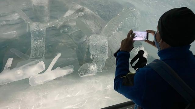 Eine Person fotografiert eine Eisskulptur