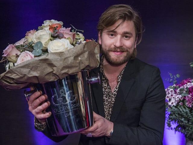 Baschi mit Blumenstrauss auf Bühne.