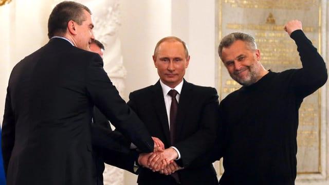 Drei Männer, darunter Wladimir Putin, geben sich die Hände. Der Mann rechts im Bild streckt die Faust in die Höhe.