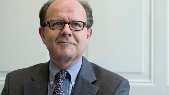 Frontalaufnahme von Vez, er trägt eine Brille, Anzug und Krawatte.