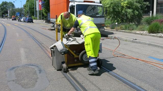 Zwei Arbeiter schleifen mit einer Maschine an einem Gleis.