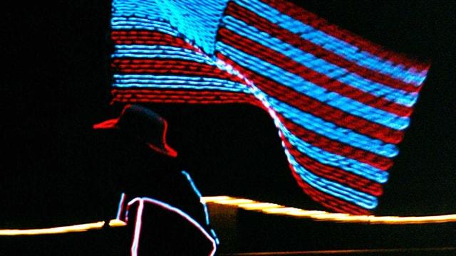 Neonbeleuchtete Frau mit Cowboy-Hut hält Flagge der USA.