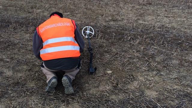 Ein Mann kniet mit einem technischen Gerät in der Wiese.