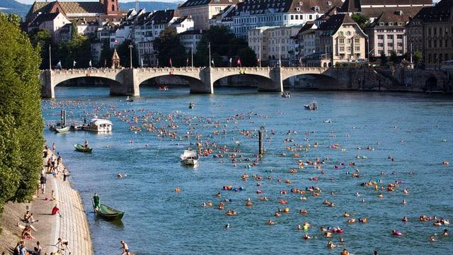 Blick auf den Rhein mit vielen Schwimmern mit buntem Schwimmsack