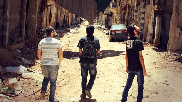 Drei Männer laufen durch Ruinen.