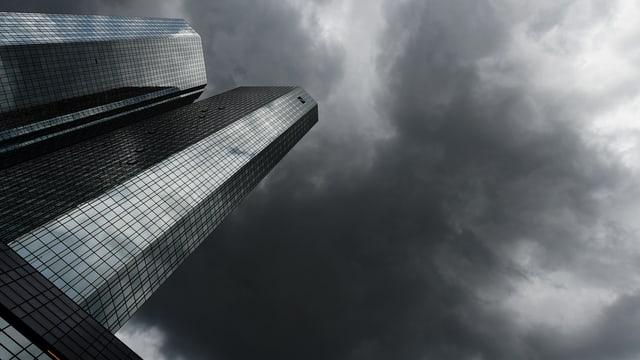 Gebäude der Deutschen Bank mit dunklen Wolken am Horizont.