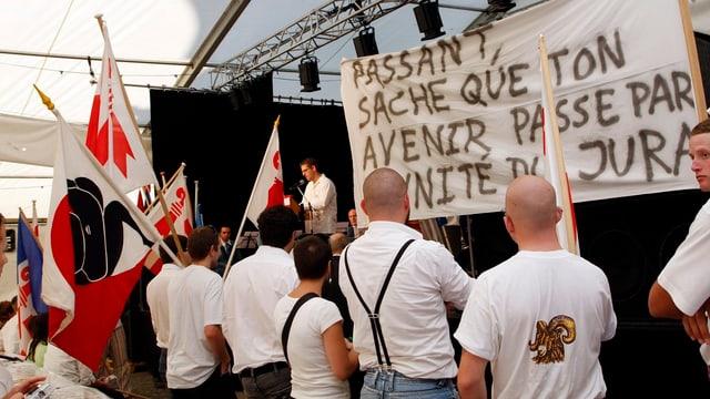 Mehrere Personen der Autonomiebewegung Mouvement autonomiste jurassien werben mit Plakaten fürn ihre Anliegen.