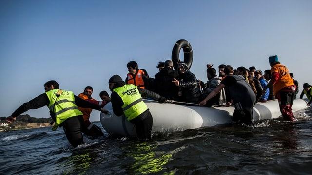 Mindestens acht Personen, eils mit gelben Signalwesten, bringen ein grosses Gummiboot, das voll ist mit Flüchtlingen, an Land.