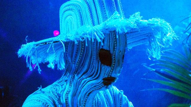 Björk mit weissem Stoffhut und Stoffmaske.