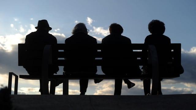 Eine Sitzbank mit vier Rentner und Rentnerinnen im Gegenlicht.