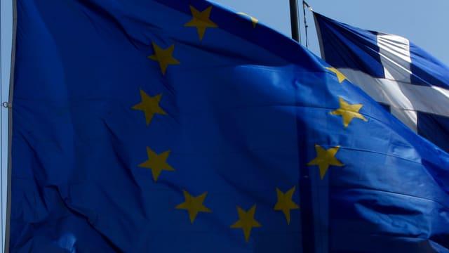 Eine EU-Flagge überdeckt eine Griechenland-Flagge.