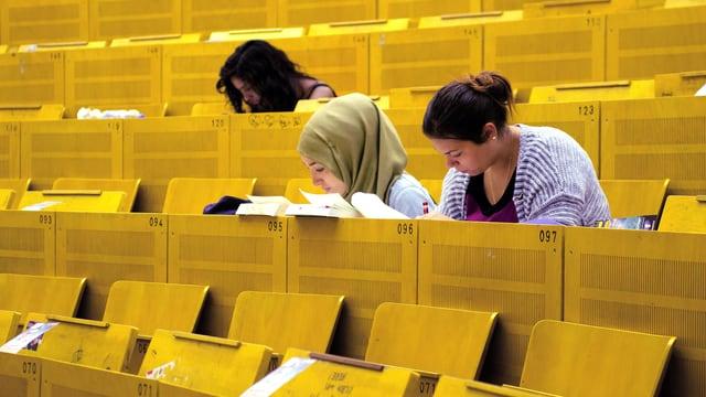 Drei Studentinnen schauen im Vorlesungssaal in ihre Bücher.
