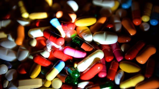 Verschiedene farbige Pillen auf einem Haufen.