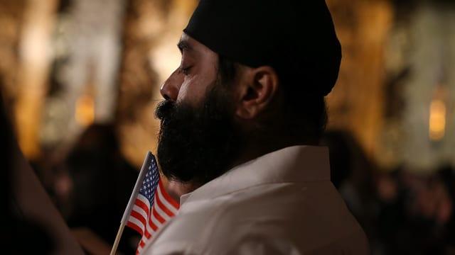 Ein Mann mit einem Turban hält eine amerikanische Flagge.