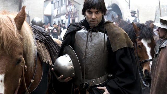 Ein Mann, in einer Rüstung, steht neben einem Pferd