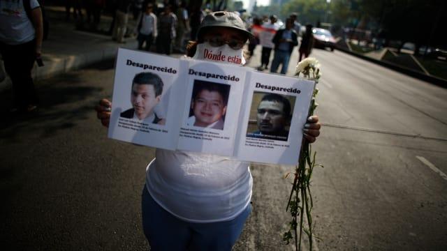 Eine Frau hält die Fotos von ihren drei vermissten Söhnen.