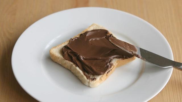 Ein mit Nutella bestrichener Toast liegt auf einem weissen Teller.