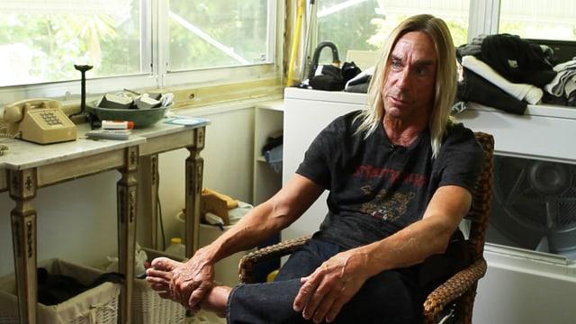 Iggy Pop sitzt in einer Wohnung auf einem Stuhl.